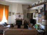 Franz házának nappalija. Könyvek, festmények, kandalló. Plazmatévé is van, de átmérője sokkal kisebb mint a könyvek térfogata...