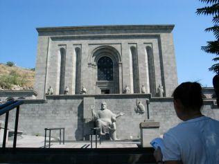 """Matenadaran, az ősi örmény kéziratok gyűjteményének helye. Gondoltuk, meglátogatjuk Borbély Lászlót (Zsebian), akit Laping Mihály kolozsvári állatorvos barátom ajánlott. Az unokatestvére. Szamosújváron (Armenopolis) született, majd hat évvel ezelőtt """"hazatért"""" az anyaországba. Rengeteget tanultunk tőle, hatalmas szerencsénk volt vele. Érkeztünkkor egy magyar turista csoport éppen az ő idegenvezetői szolgáltatását igényelte. Hozzájuk csapódtunk mi is... Az épület előtt az örmény ábécé megalktója, Meszrop Mastoc tanítványával. Mastoc 405-ben alakotta meg az örmény ábécét. Laci szenvedélyesen beszélt az ókori kéziratokról, azok megőrzéséről. Ez a szenvedély, az örménységgel kapcsolatos minden vonatkozású hazafiasság végigkísérte és meghatározta a vele töltött időnket, amelyből – szerencsére – sok adatott"""