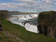 A parkolás után hirtelen előtűnő impozáns Gulfoss vízesés elkápráztat. Hosszú percekig nézem, még magamba sem tudok beszélni a meglepetéstől. A tömbház magasságú vízeséssel kapcsolatos érdekes történet olvasható a helyszínen: innen indult Izland első környezetvédelmi mozgalma. Az 1920-as években vízerőművet próbáltak létrehozni, de Sigríður Tómasdóttir, az egyik befektető lánya ellenszegült. Szerencsére a vízesést és környékét 1979-ben természetvédelmi területté nyilvánították, így a tervezett befektetés meghiúsult. Az országban továbbra is nagy a nyomás a természet adta energiaforrások kihasználására, de amint azt több helyen láthattuk kiplakátolva, jelenleg Izland szükségleteinek 100 százalékát (!) környezetkímélő forrásokból meríti: geotermális, szél, hő- és vízenergia felhasználásával. A napsütés csodálatos szivárvánnyal öleli át ezt a természeti csodát. Még a legkevésbé romantikus férfi is elérzékenyül a látványon..